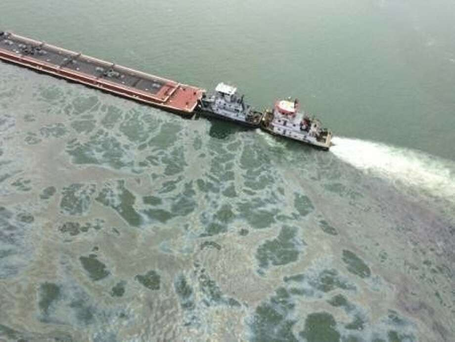 A barge loaded with marine fuel oil sits partially submerged in the Houston Ship Channel, March 22, 2014. The bulk carrier Summer Wind, reported a collision between the Summer Wind and a barge, containing 924,000 gallons of fuel oil, towed by the motor vessel Miss Susan. Photo: Courtesy U.S. Coast Guard