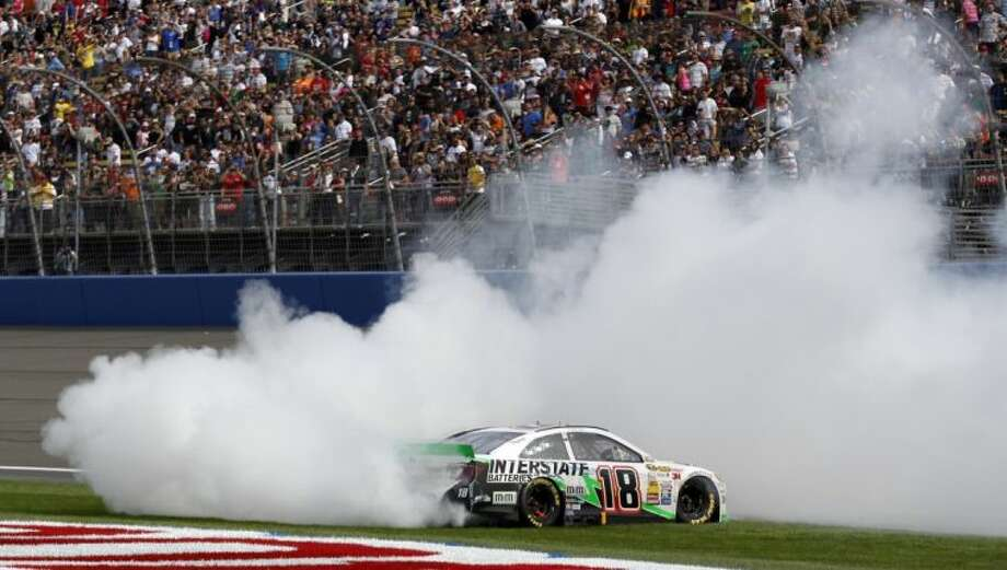 Kyle Busch (18) does a burnout after winning the NASCAR Sprint Series auto race in Fontana, Calif.