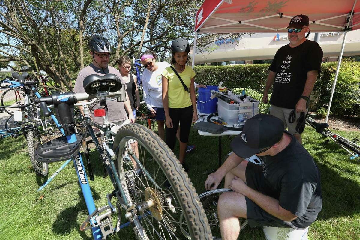 Roger Selin, Nay Selin, Anne Selin and Nicole Selin watch Chain Reaction Ministries' Jeff Stones fixing one of their bikes during Sunday Streets on Eldridge Parkway Sunday, Oct. 2, 2016, in Houston. Behind Stones was Rev. David Rinklea from the ministries.