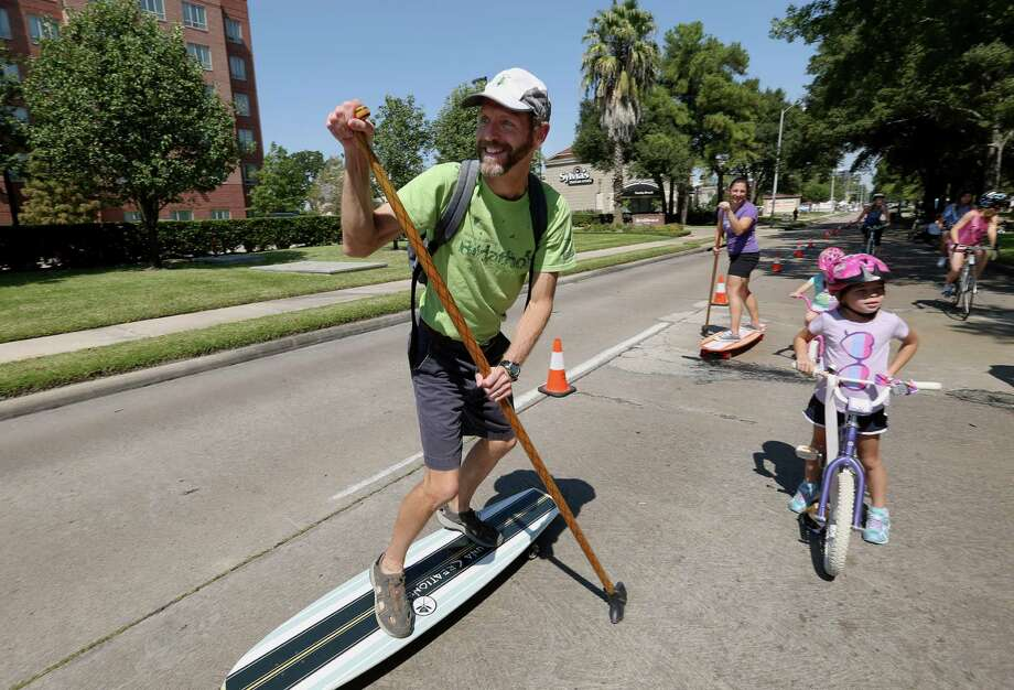 Is Sunday Streets headed in the right direction? In this photo: Brad Moore and his wife, Monika, paddle long boards with their daughters on the Sunday Streets in the Energy Corridor. Photo: Yi-Chin Lee, Houston Chronicle / © 2016  Houston Chronicle
