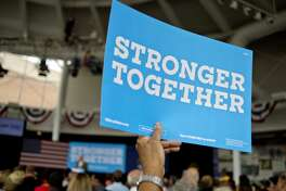 A supporter holds up a Hilary Clinton campaign sign as former President Bill Clinton speaks during a rally on Monday at the Dow Events Center in Saginaw. Clinton visited Michigan to campaign for his wife Hillary.