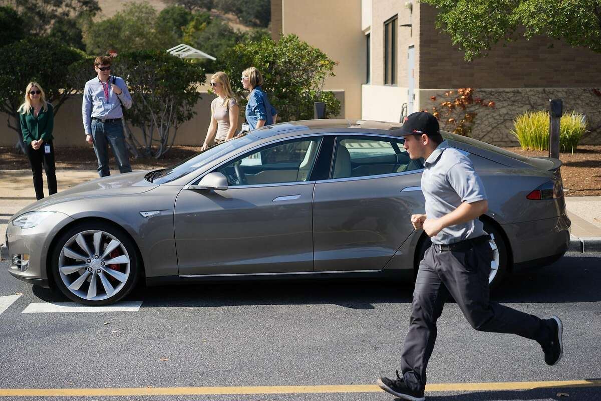 Members of the press and Telsa employees look at a Tesla with newly upgraded software at Tesla in Palo Alto, Calif. on Wednesday, Oct. 14, 2015. An update to Tesla's Autopilot system will aide drivers in changing lanes, parking and steering.