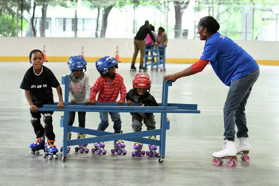 City Recreation worker Anna Nyambwe, right, helps children learn to roller skate on Friday, Sept. 30, 2016, at Swinburne Skating Rink in Albany, N.Y. The rink will be open for roller skating for the next two months. Hours are Monday through Friday from 3 to 9 p.m. and weekends from 1 to 9 p.m. Admission for children and seniors is $1 and $2 for adults. Roller skate are available to rent for $3 or you can bring your own. Helmets are available to borrow. (Cindy Schultz / Times Union) Photo: Cindy Schultz / Albany Times Union