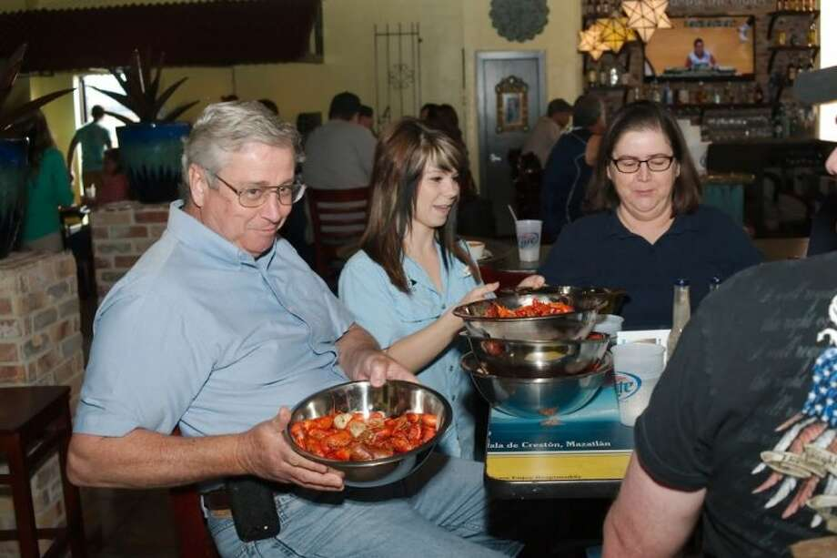 Bob Watkins shows off a bowl of boiled crawfish delivered by waitress Krystal Ogg during the Mex-sea-co, 1853 Pearland Pkwy grand opening Saturday, March 22. Photo: KIRK SIDES