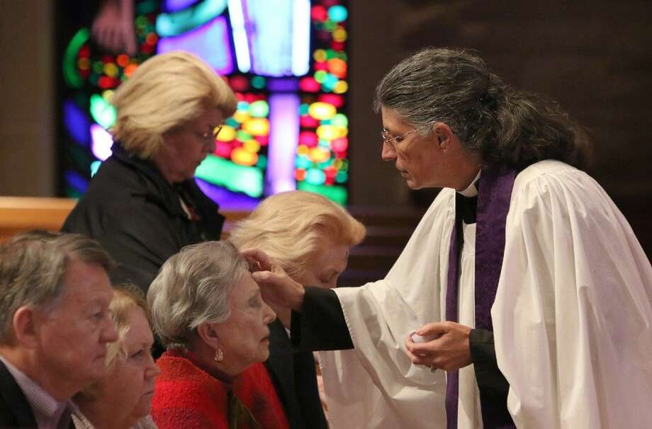 Rev. Janet Dantone marks the foreheads of members of the congregation during Ash Wednesday at The Church of St. John The Divine in Houston, Texas on Wednesday, February 18, 2015. To view or purchase this photo and others like it, go to HCNPics.com. Photo: Staff Photo By Alan Warren