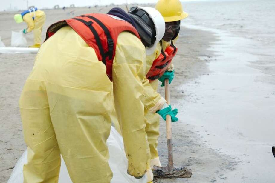Workers scoop up clumps of oil-soaked sand along the beach in Texas City during a clean up effort Monday, March 24, after a barge struck a cargo ship near the Dike. Photo: KIRK SIDES