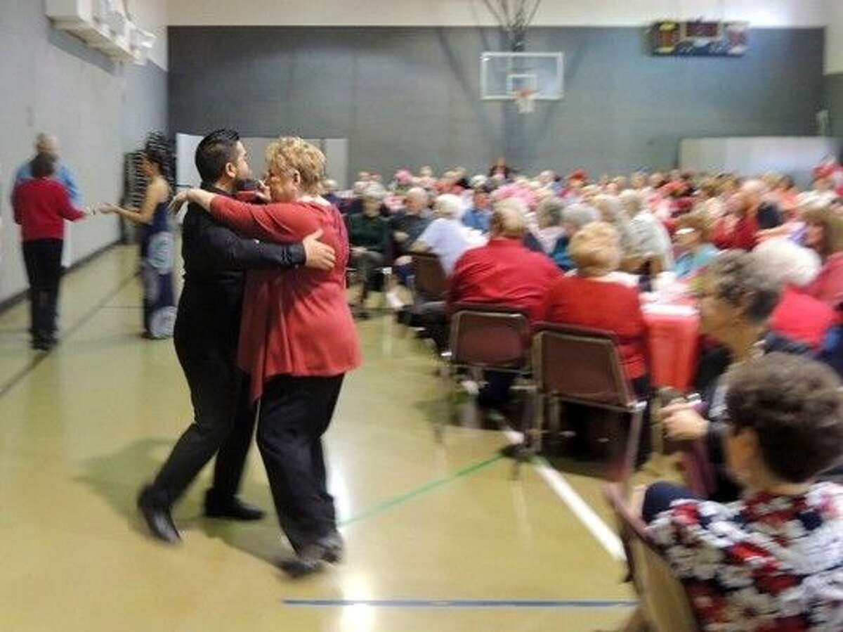 A performer from the Arthur Murray Dance Studio in The Woodlands dances with attendees at Precinct 4's recent luncheon at Jersey Village Baptist Church.