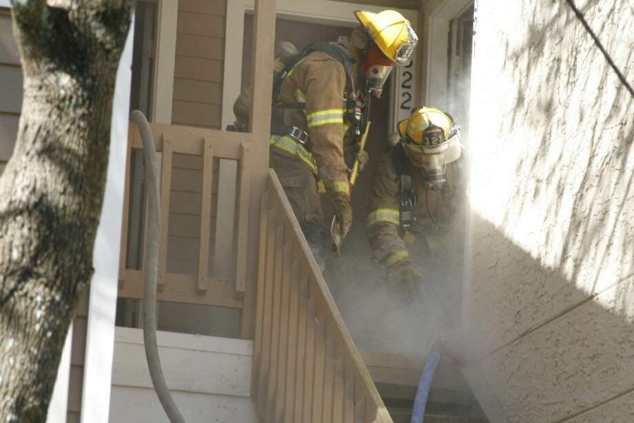 Two Porter Fire Department firefighters work to pull a hose into an apartment complex during their training exercises at the abandoned Kings Crossing Apartment complex in Kingwood.