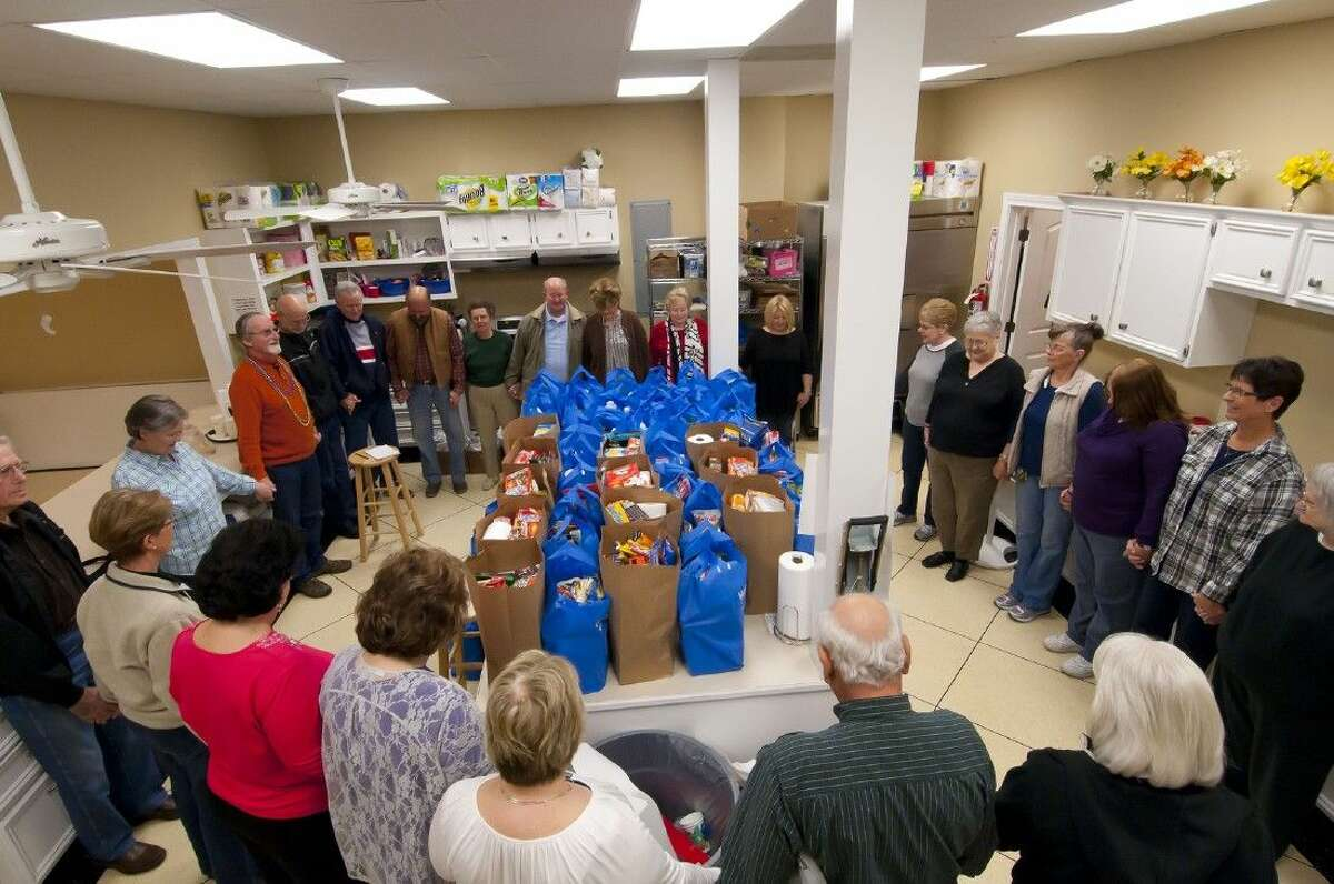Volunteers for Lydia's Food Pantry pray before distributing groceries on Tuesday, Feb. 17.