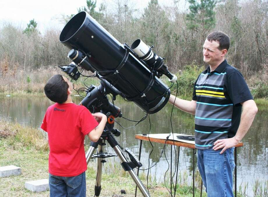 Cleveland resident Duane Mizell shares his love of astronomy with son, Lonnie. Photo: Stephanie Buckner