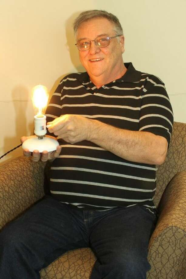 Larry Simmons, of Onalaska, stopped by Sam Houston Electric Cooperative's Livingston office with his 100-year-old GE National Mazda light bulb. Photo: Submitted Photo