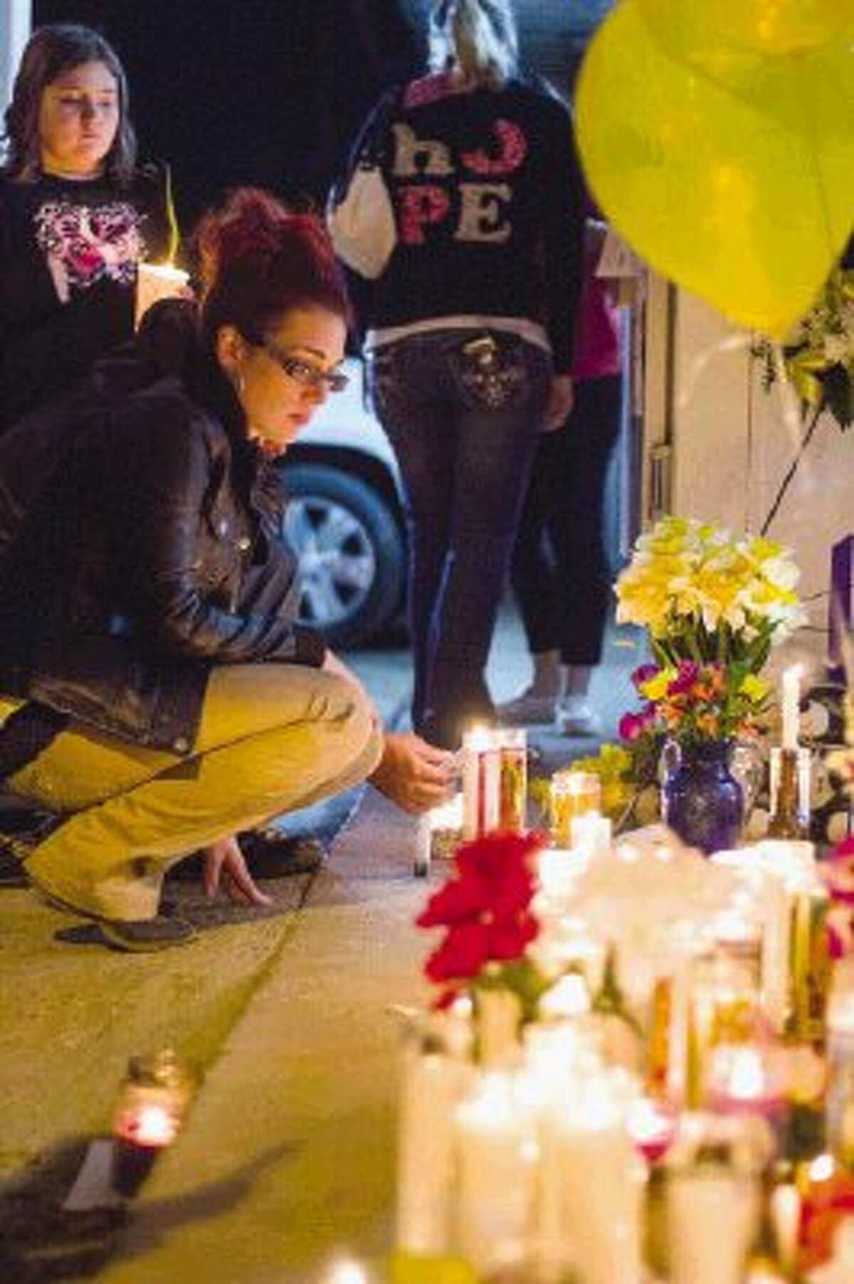 """Christina Smith lights a candle during an impromptu vigil for Shamsuddin """"Sam"""" Sadruddin, a store owner who was killed during a robbery attempt Monday night at the Shell service station and convenience store in the 18300 block of Texas 105 East."""