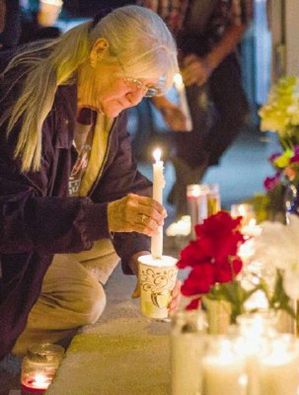 """Deborah Noble places a candle inside a cup Tuesday night during an impromptu vigil for popular store-owner Shamsuddin Sadruddin, who community members all knew as """"Sam."""" Sadruddin was shot to death during a robbery Monday night at the Shell service station and convenience store he owned at 18374 Texas 105 East."""