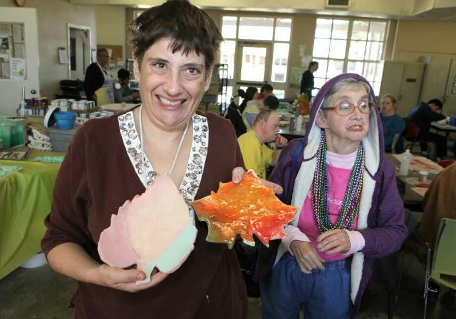 Brookwood citizen Michele with ceramic leaves at two different stages at The Brookwood Community in Brookshire. Photo: Alan Warren
