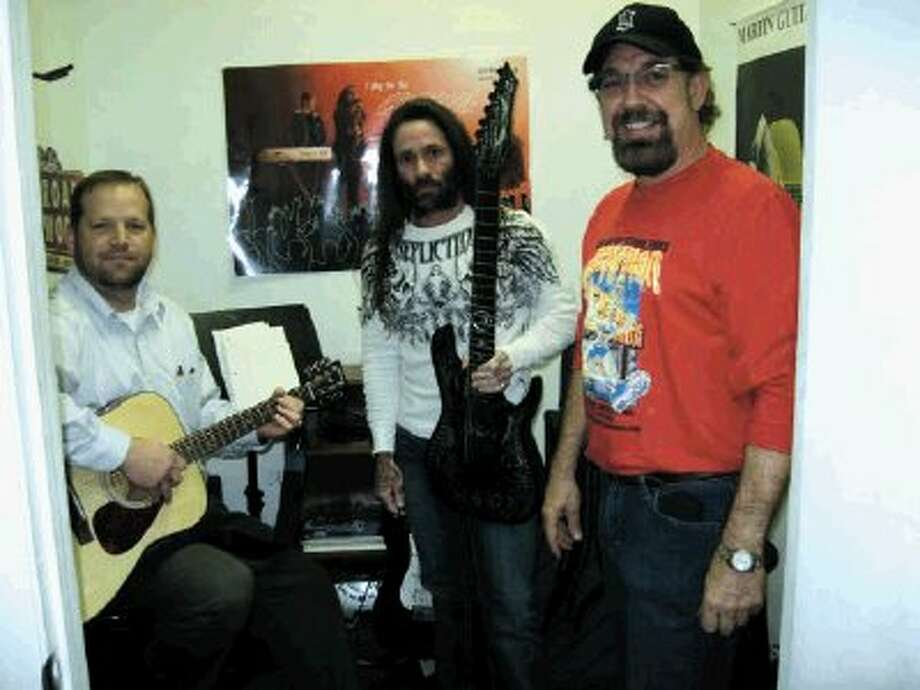 """Guitar legend Rusty Cooley is now teaching guitar lessons at Texas Music Emporium two days a week. Pictured with Cooley, center, are Texas Music Emporium owner """"Jim Rod"""" Cappiello, right, and Allen White, left."""