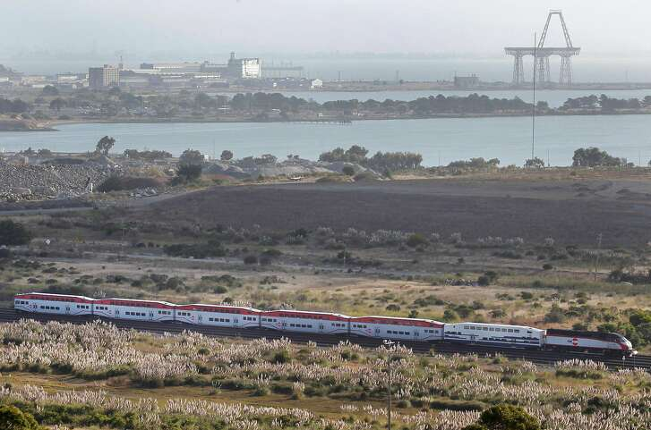 A Caltrain train travels through the middle of open space land between Bayshore Boulevard and Highway 101 in Brisbane, Calif. on Thursday, Sept. 3, 2015. The Baylands mixed-use development project is planned for the 660-acre site.