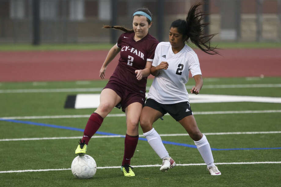 Cy-Fair forward Sarah Hluza (2) struggles for possession of the ball with Alief Hastings defender Joanna Canil (2) during the girls' soccer playoff game Thursday at Crump Stadium. To view or purchase this photo and others like it, go to HCNPics.com. (Michael Minasi/HCN) Photo: Michael Minasi
