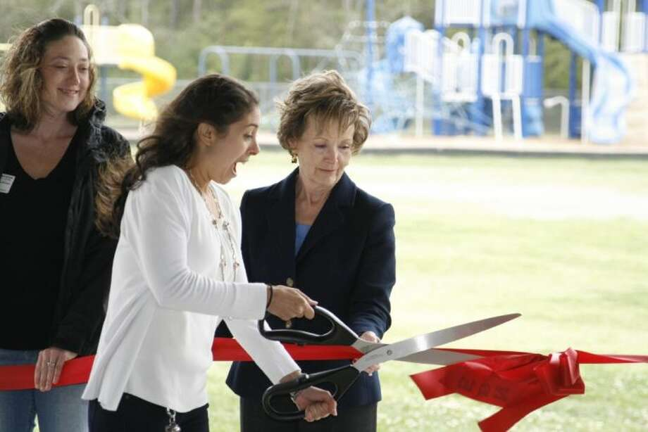 Former North Belt Elementary teacher Andrea Barela, who now teaches at Lakeshore Elementary, cuts the ribbon at the ceremony for North Belt Elementary's new playground March 26, 2014.