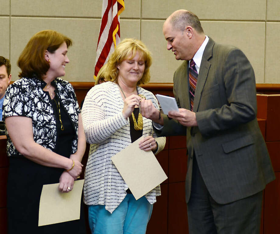 Dr. Mark Henry, superintendent of schools, presented the Superintendent Challenge Coin to Spillane Middle School staff members Sean Stiewert, left, and Becky Cushen during the March 13 Board of Trustees meeting.