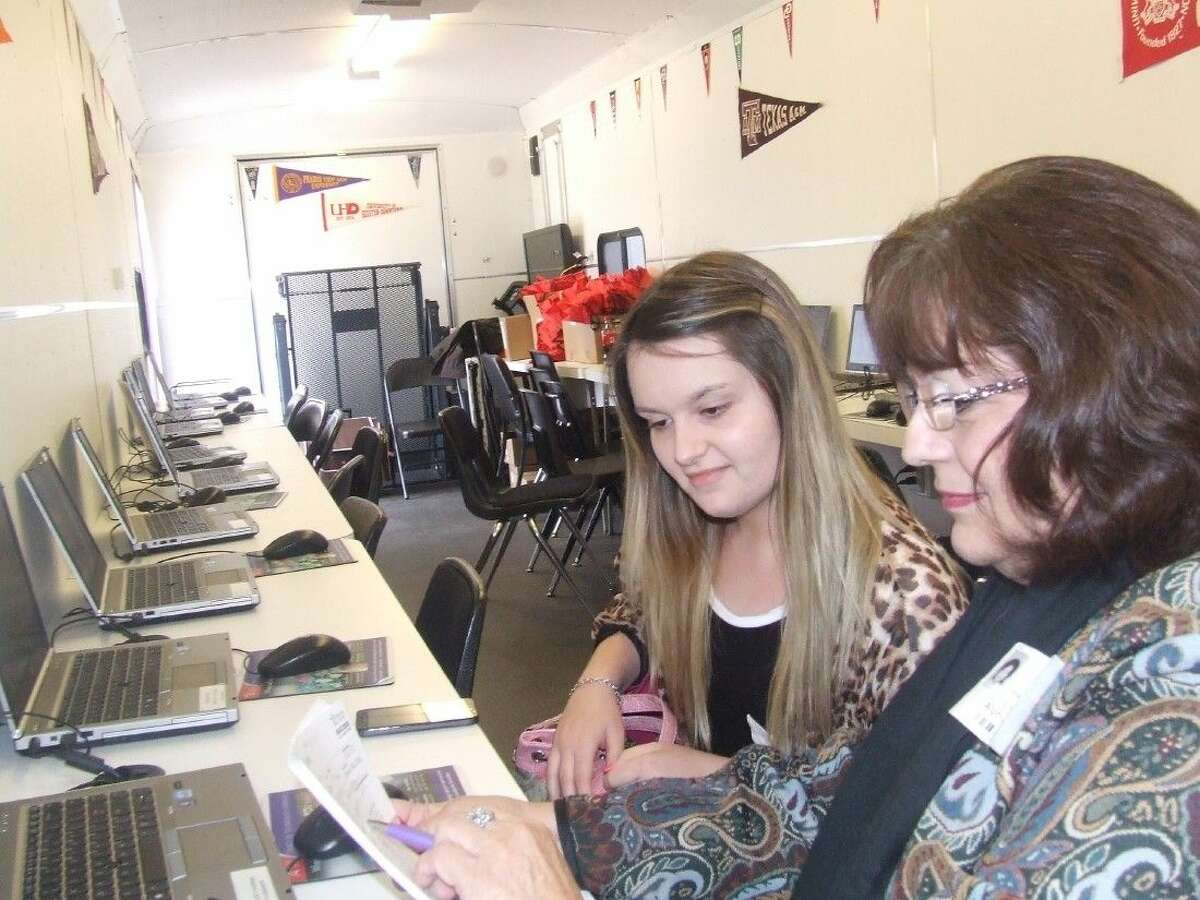 Dr. Irene Briggs helps Chaslin Holbert, a junior at Alpha Academy in Magnolia, with information on registering for Lone Star College on Tuesday, Feb. 24.