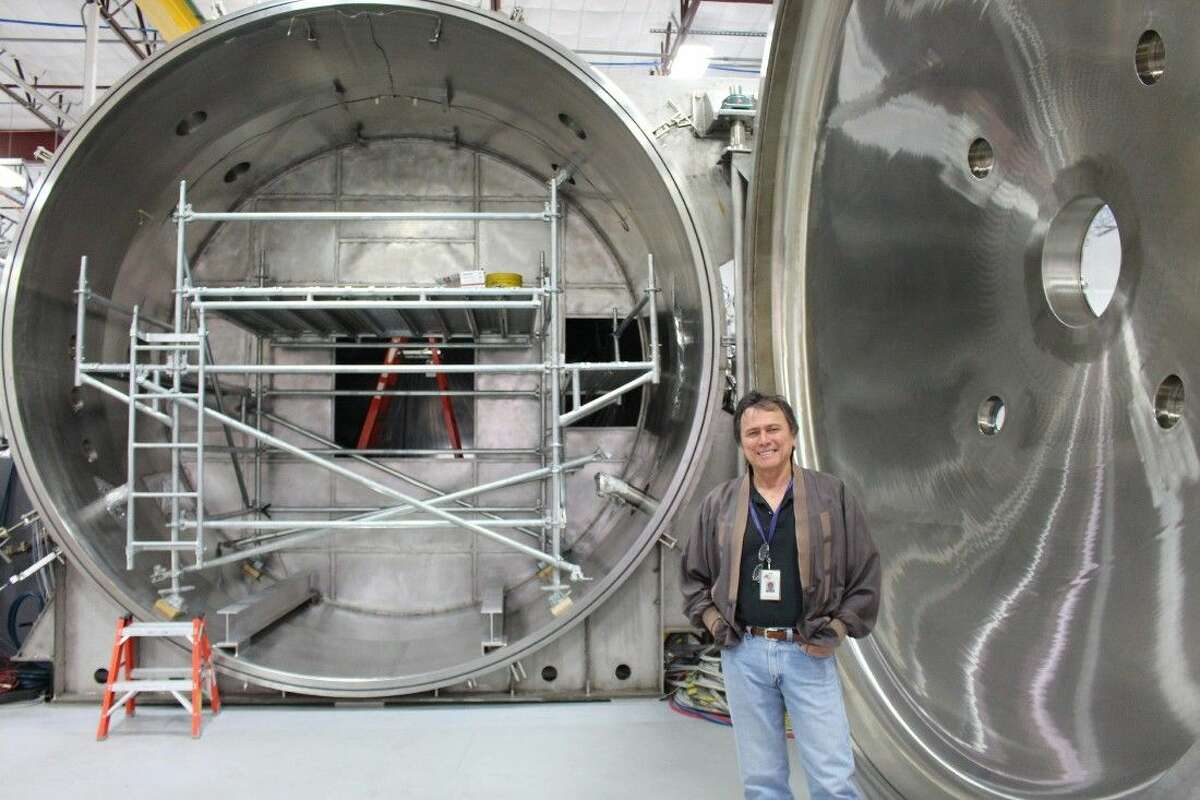 Dr. Chang-Diaz stands in front of the vacuum chamber that holds his plasma rocket.
