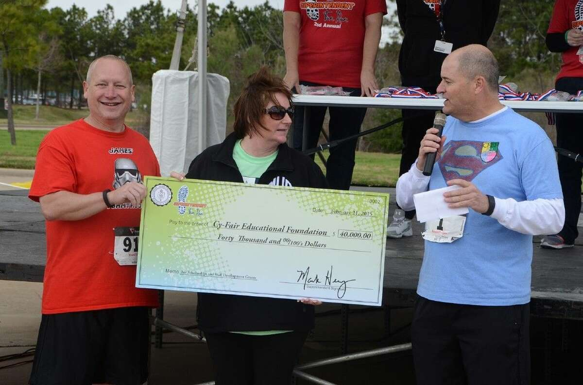 Board of Trustees President Don Ryan, left, and CFISD Superintendent Dr. Mark Henry present Marie Holmes, executive director of the Cy-Fair Educational Foundation, with a check worth $40,000 from the Second Annual Superintendent Fun Run on Feb. 21.