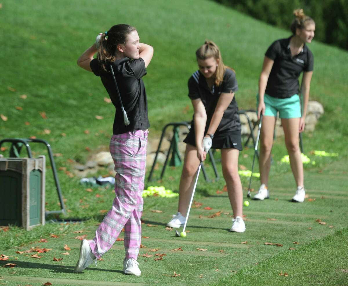 Sacred Heart junior Morgan Hennessy, left, and others hit the driving range during the Sacred Heart Greenwich annual golf and tennis outing at Greenwich Country Club in Greenwich, Conn. Monday, Oct. 3, 2016.