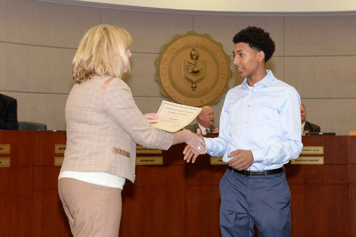 Board of Trustees secretary Christine Hartley presents Cypress Ranch High School junior Miles Simms with an outstanding achievement award for his Kicks 4 Kidz shoe donation campaign.