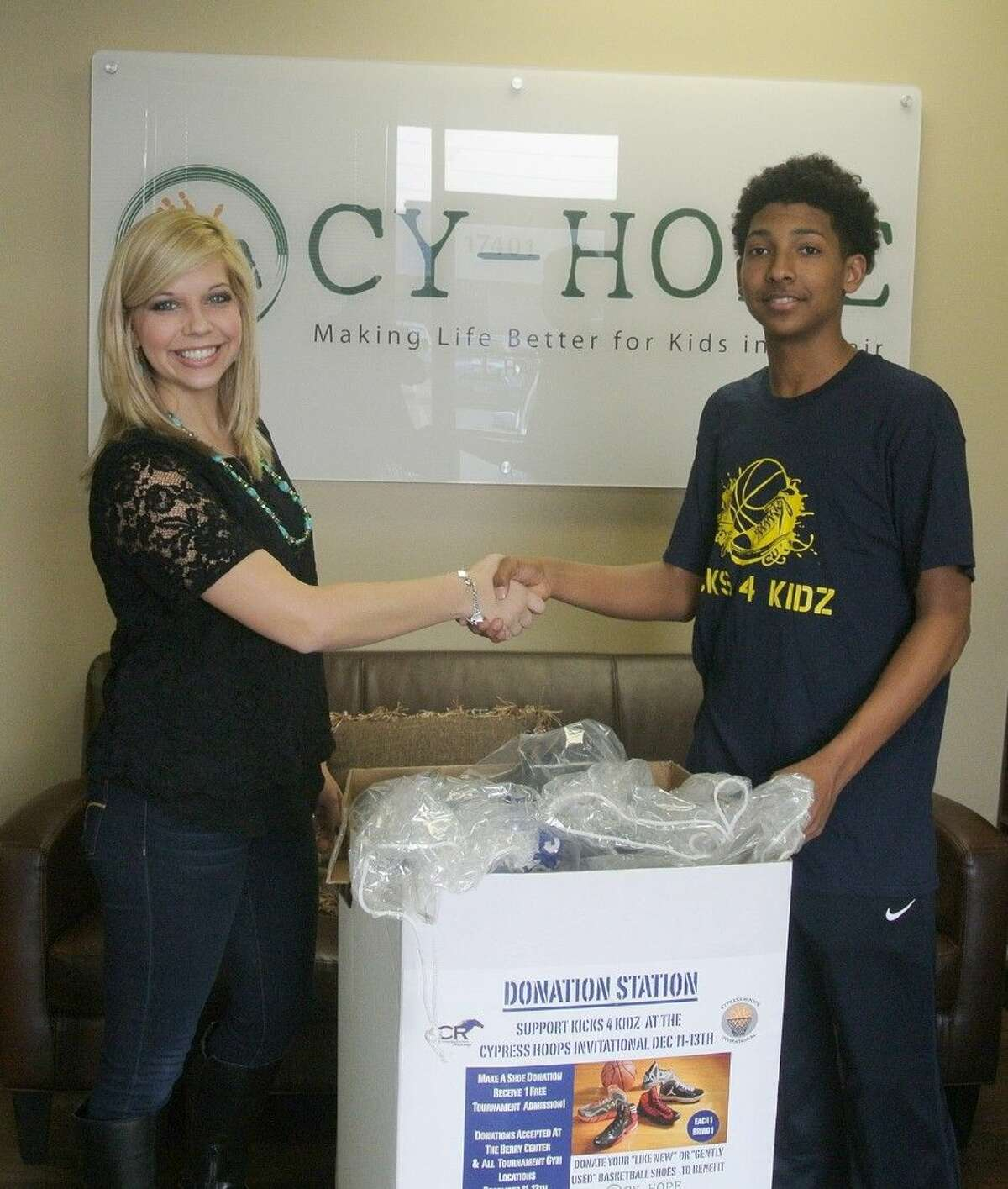 Cy-Hope counseling center employee Sarah Henry thanks Miles Simms for the shoe donation his program Kicks 4 Kidz generated for children in the nonprofit's Hope Centers.