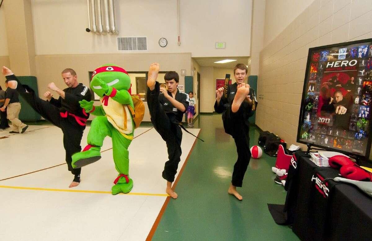 Representatives of Hero Martial Arts Academy demonstrates their kicks at the Color/Walk Run Health Fair at Bernshausen Elementary on Saturday, Feb. 21.