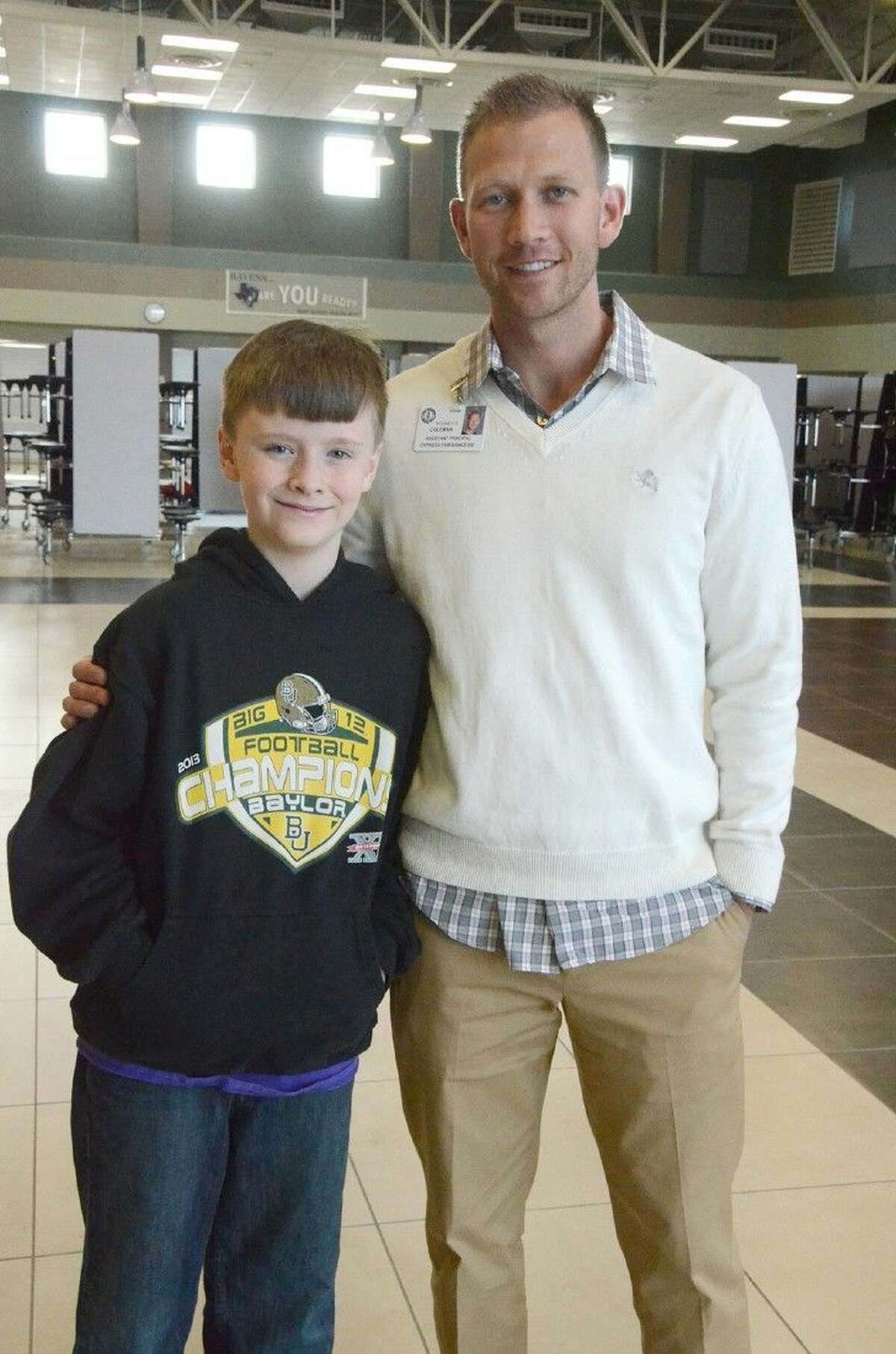 Anthony Middle School Assistant Principal Blake Coleman and student Grayson Barger stand in the cafeteria where, just days before, Coleman saved Barger's life by performing the Heimlich maneuver.