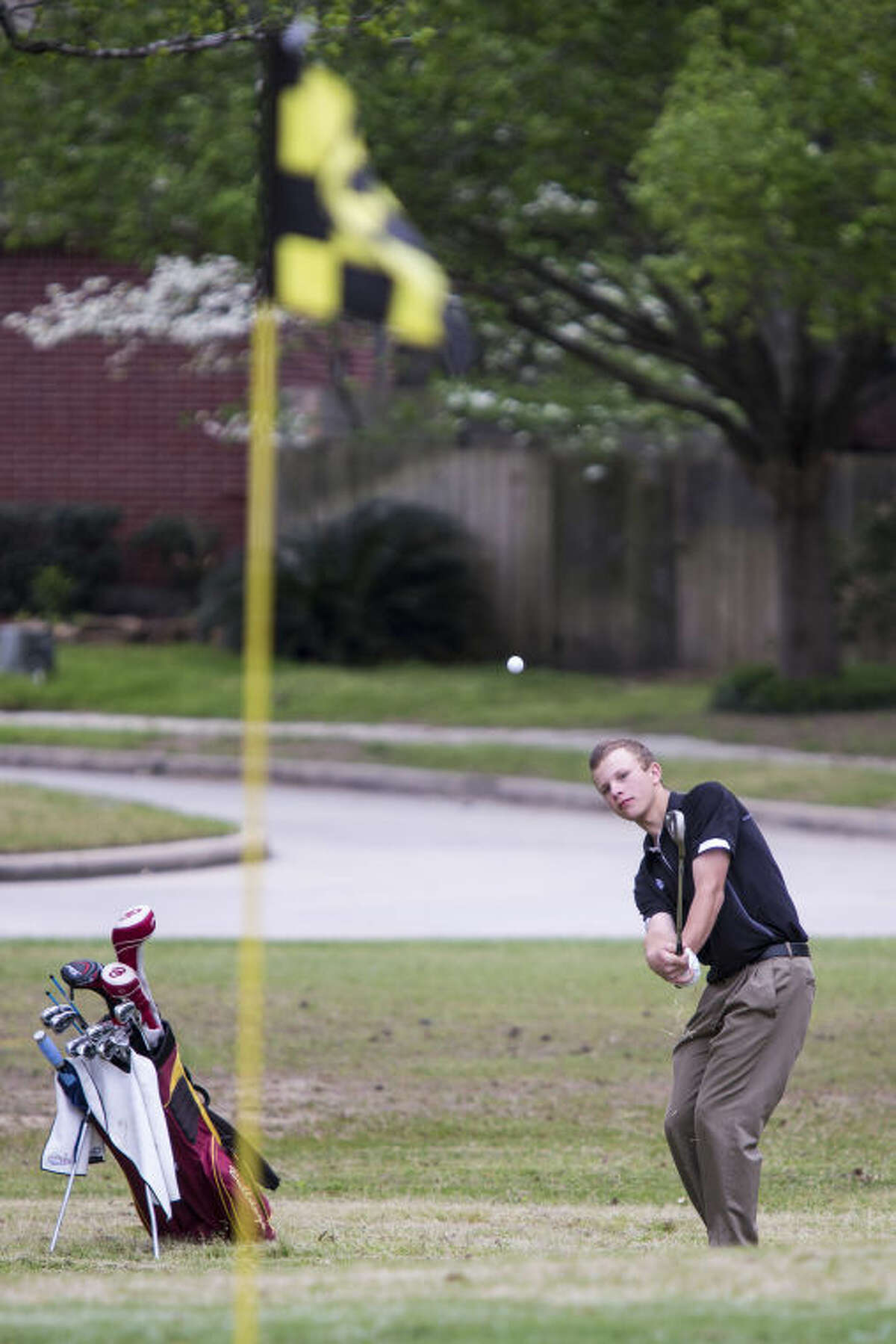 Summer Creek's Johnathan Carr chips onto the green during the District 19-4A tournament March 26, 2014, at Oakhurst Golf Club. (Photo by ANDREW BUCKLEY/The Observer)
