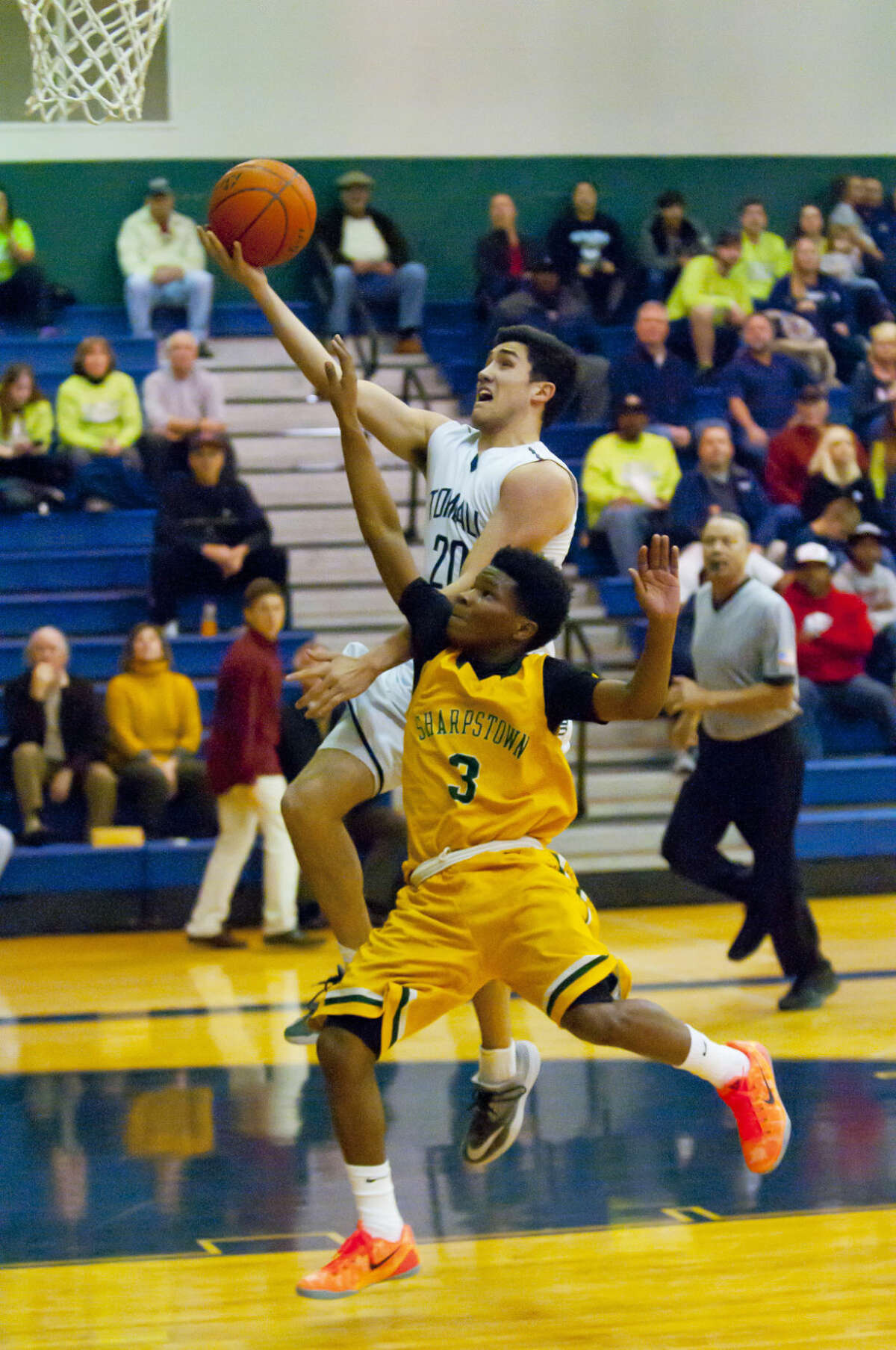 Matt Avila (No.20) goes high for a layup against Sharpstown's William Watkins (No.3) helping Tomball Memorial to their first ever playoff victory.