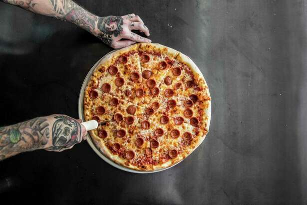 A pepperoni pie from Pi Pizza, cut by tatted chef Anthony Calleo. Pi Pizza is set to open at 181 Heights.