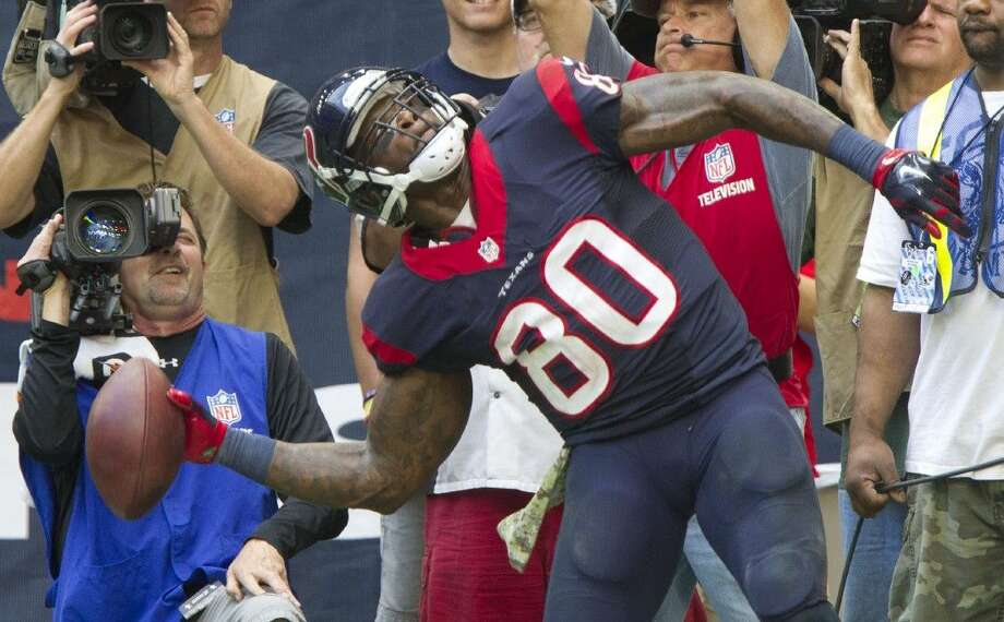 Houston Texans wide receiver Andre Johnson throws the ball into the stands in celebration after catching a 4-yard touchdown pass on Sunday against the Titans. Photo: Jason Fochtman