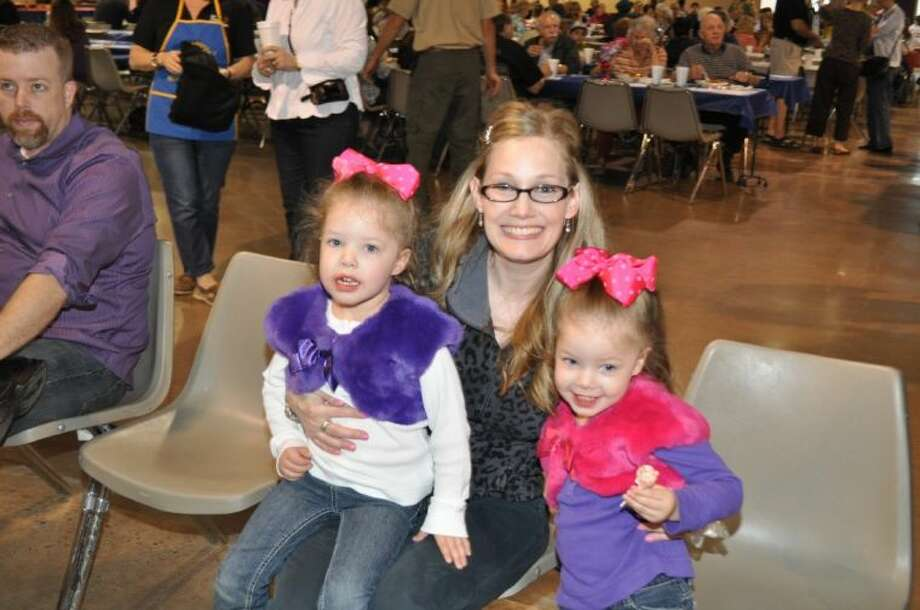 Four-year-old Abagail Brownlee (R) was a winner at the Rotary Fish Fry by correctly guessing the number of erasers in a jar. She won the jar of erasers and a gift card to McDonalds. She is joined by her mother Cari and her twin sister Emily (L). Photo: BILL WELCH