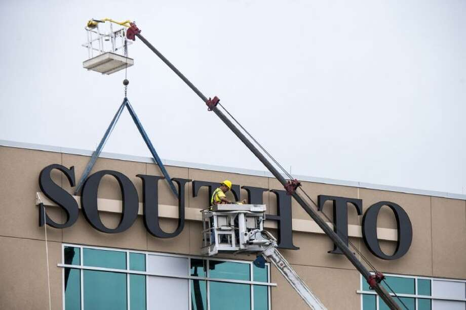 Construction workers install a sign for the new South Tower at Kingwood Medical Center. Photo: ANDREW BUCKLEY