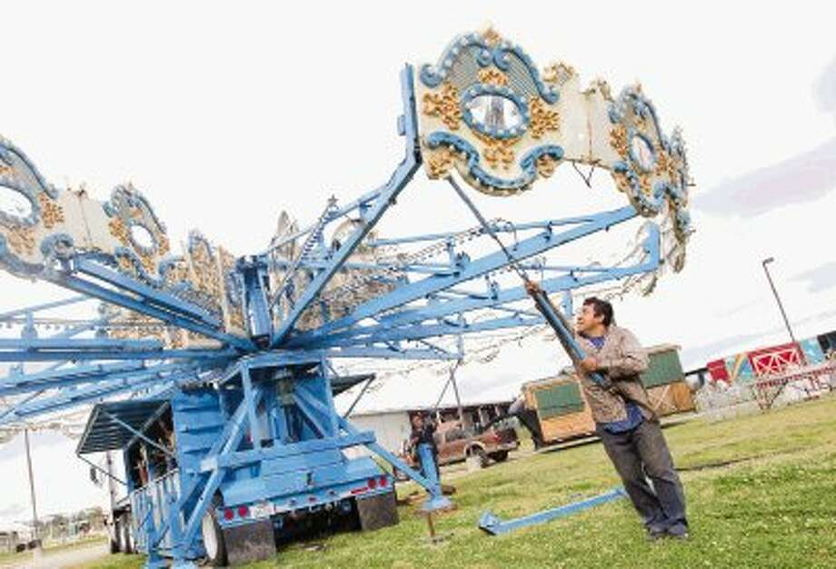 A carnival worker helps set up a Merry-Go-Round at the Montgomery County Fairgrounds Thursday morning. The 57th annual Montgomery County Fair & Rodeo kicks off today. Photo: Jason Fochtman / Conroe Courier / HCN