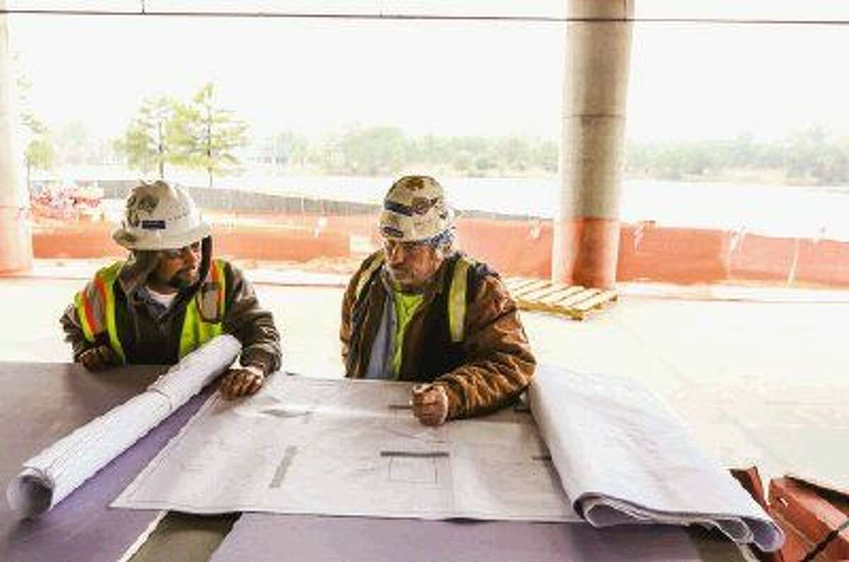 Construction workers review plans for Three Hughes Landing, a 12-story, 321,000-square-foot Class A office building opening in October.