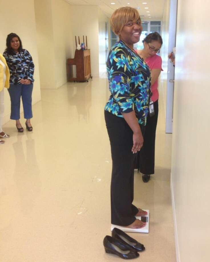 Houston ISD's Administrative Services Manager Reba Jelks joins other employees in a weigh-in as part of the HealthyWage Challenge, a four-month incentive program that pays employees who lose weight.