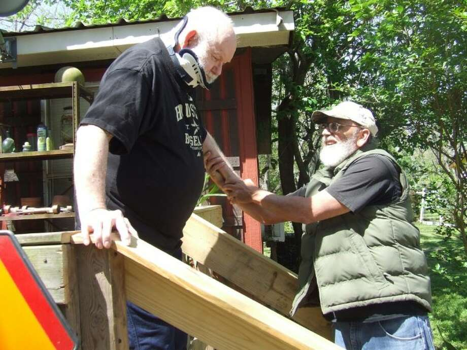 Jessie Smith holds on to his new handrails while getting help from his longtime friend Steven Crocker outside his house in Tomball. Faith in Action volunteers added handrails and new steps to Smith's house during its Faith In Action weekend on March 29-30.