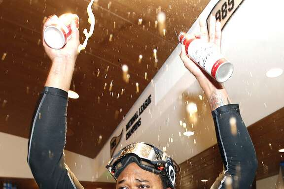 San Francisco Giants' Johnny Cueto celebrates in the clubhouse after the team clinched the National League's second place, wild-card spot following their 7-1 win over the Los Angeles Dodgers in a baseball game in San Francisco, Sunday, Oct. 2, 2016. (AP Photo/Tony Avelar)