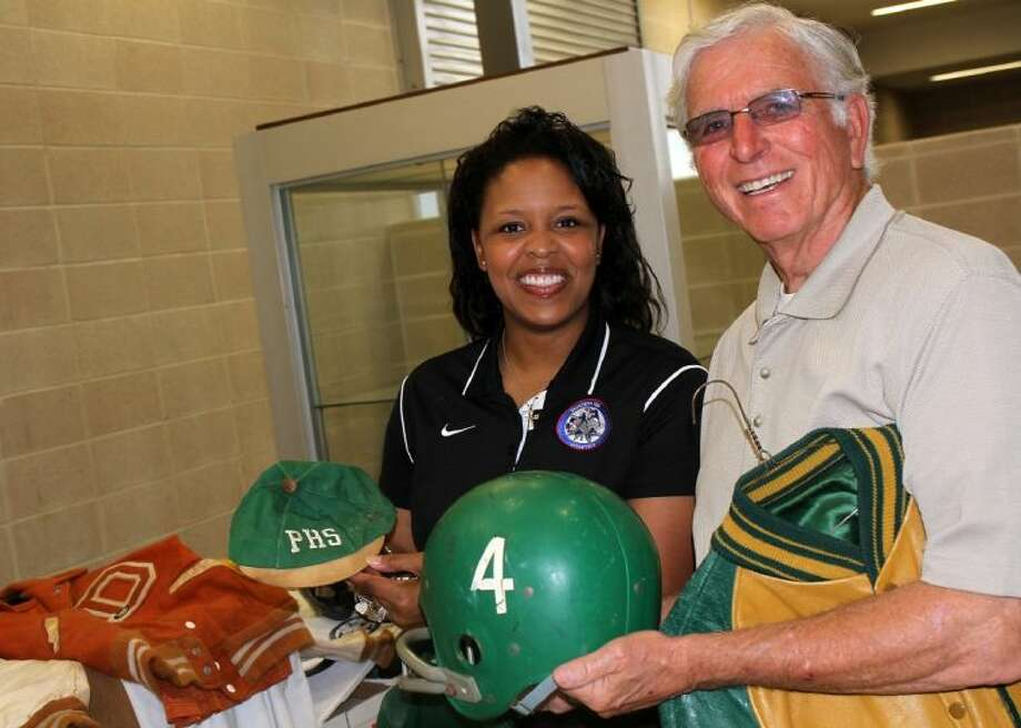 Roneka Lee and George Cheshire marvel at some of the memorabilia donated by Hall of Fame inductees, including Randy Kerbow, who contributed his Pasadena High beanie and his helmet from the 1958 season. The 1958 Eagles are the only Pasadena ISD team to play in a state football championship game. Photo: Courtesy Pasadena ISD