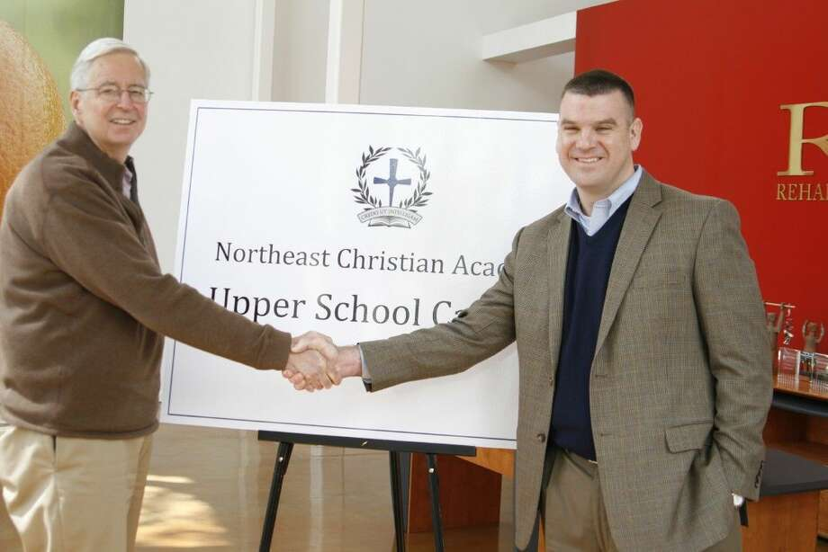 Bob Rehak of Rehak Creative Services, left, shakes hands with Brad Baggett, Northeast Christian Academy Head of School, at the site where the NCA Upper School will be located.