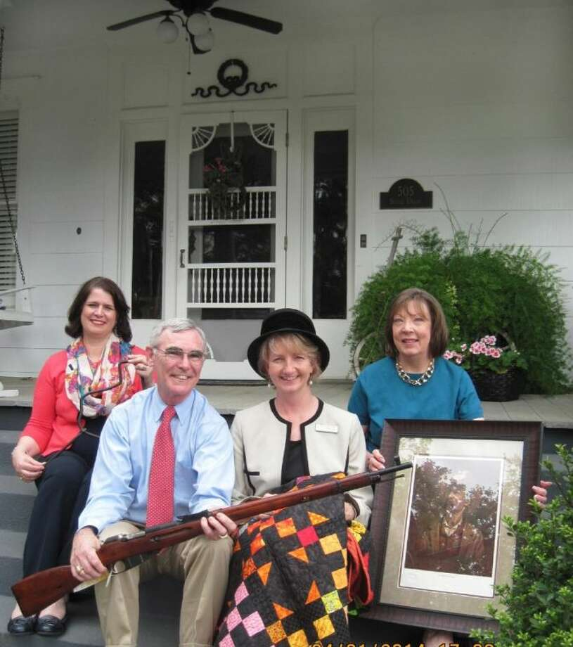 "Sitting on the front porch steps of the historic Victorian home of Billie Van Slyke are Melody Hess, with major sponsor New First National Bank and co-chair of the Event Committee; Charles Hewitt, with major sponsor OCuSOFT; Claire Rogers, executive director of the Fort Bend County Museum Association; and Lynn Hewitt, chair of the Event Committee. They are showing off some of the donated auction items for Lone Star Stomp XXV, ""Belles and Beaux,"" taking place on April 12. The Van Slyke home itself is featured in one of the auction items. Photo: Fort Bend County Museum"