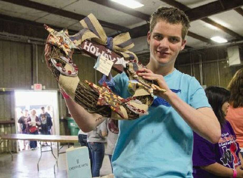 "Brett Bordelon, a Willis High School student, shows off the ""Howdy Wreath"" he entered into the 2014 Montgomery County Fair Special Education Show on Friday. Bordelon was one of the winners in the show's event this year on the opening day of the county fair. Photo: Staff Photo By Ana Ramirez / The Conroe Courier/ The Woodland"