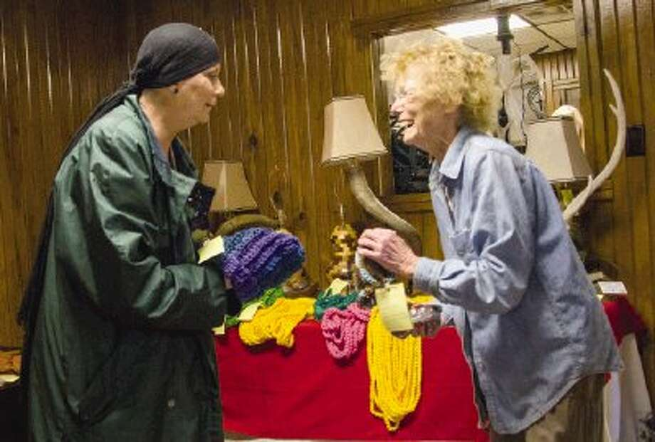 Stacey Wehner and Evelyn Jackson look at hats and scarves in The Country Store at the Montgomery County Fair and Rodeo in Conroe Friday. The store sells clothing, quilts, breads and candy. Photo: Staff Photo By Ana Ramirez / The Conroe Courier/ The Woodland