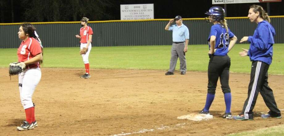 Assistant Coach Shauna Emola (right) advises Lady Pirate Abby Courvelle (19) on her next move while Lady Cat first base player Arcelia Andrade (15).