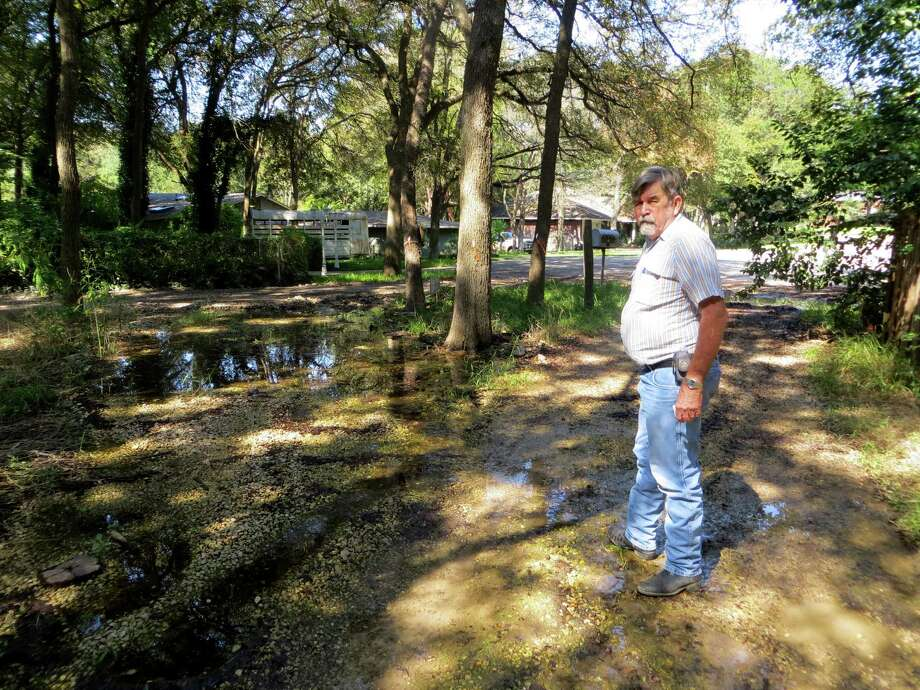 Ray Reininger says he granted the city of Seguin an easement nearly a year ago for use in redirecting the groundwater that's surfacing at the end of his driveway, but work has yet to start. He blames a city sewer project in the Oak Vallage North subdivision for causing the water to erupt where it had not previously appeared. Photo: Zeke MacCormack, Staff / San Antonio Express-News / San Antonio Express-News