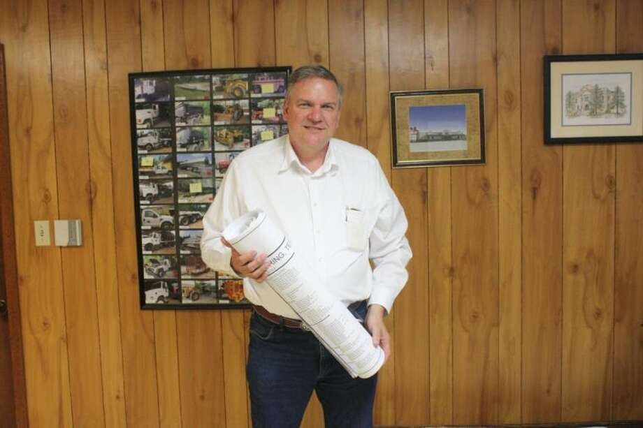 Pct. 1 Commissioner Ray McCoppin is now the liaison between San Jacinto County Courthouse and Mega Prime contractors. He is holding the prints to the new shelter on FM 150. Photo: JACOB MCADAMS